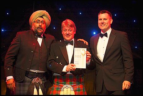 Norman Sinclair (centre) picks up the award.