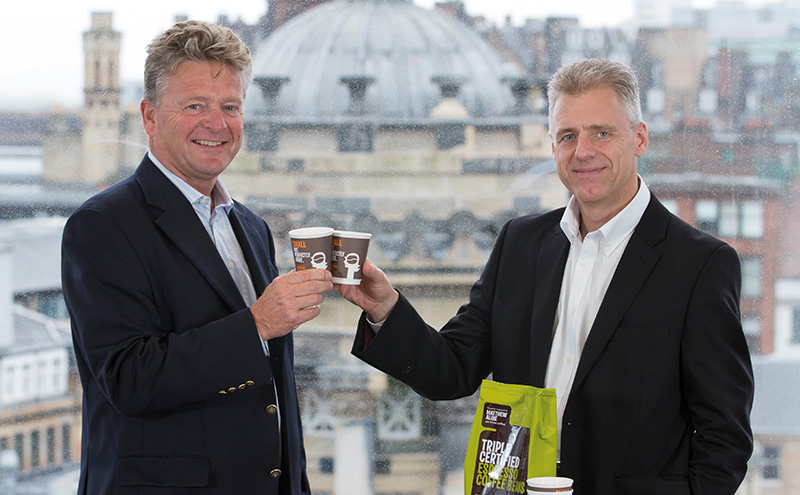 • Nick Snow (left), managing director of Tchibo Coffee Service, with Gary Nicol (right), chief executive of Mathew Algie, raising a cup to the acquisition deal.