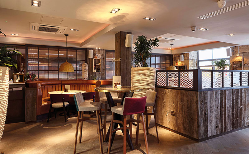 • The restaurant area includes booth seating and is separated from the bar by a glass wall.