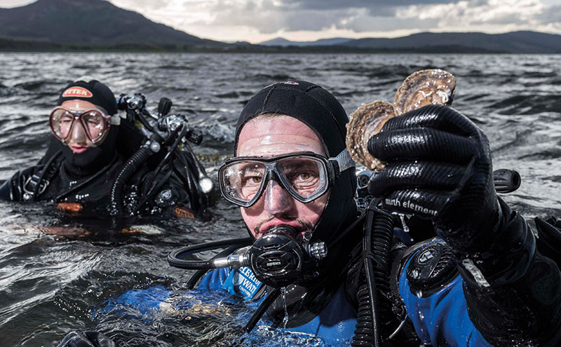 Dr Bill Sanderson (R) & George Stoyle (L) emerge from the Dornoch Firth with oysters from the Glenmorangie DEEP Project