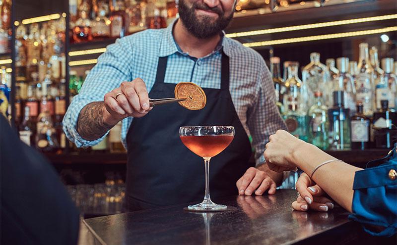 Bartender adding garnish to a cocktail.