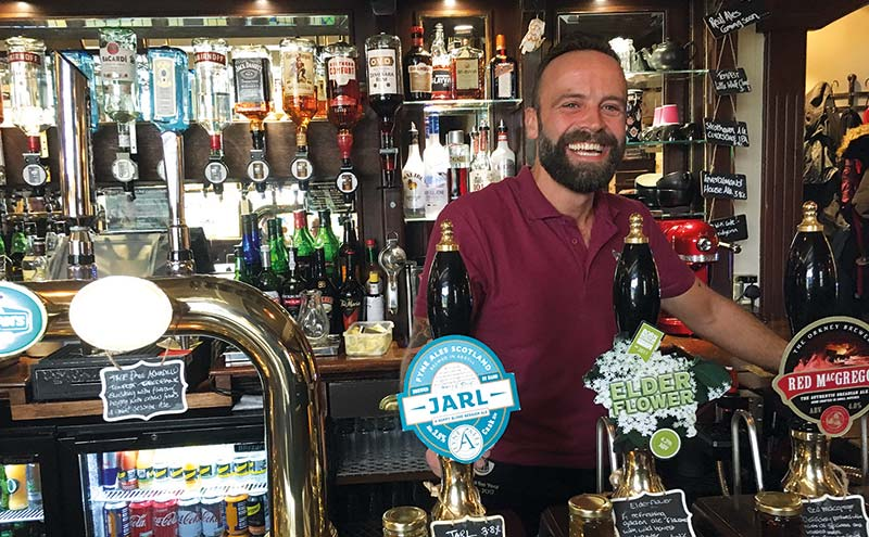 Gregor Grant behind a bar